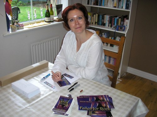 This is me, grinning like the Cheshire cat, as I'm packaging Fallen for Rock SWAG packs and other prizes...