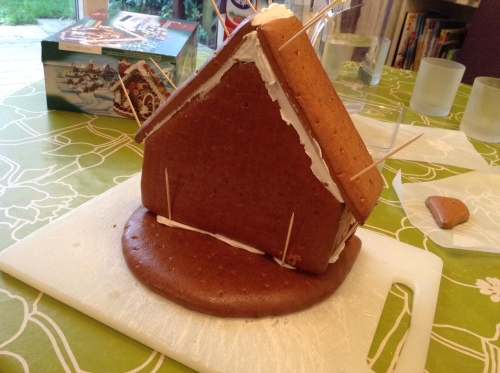 Putting the roof on. See all that white squishy stuff? That's royal icing. Never made that before; it was a real education. It's ready to use when it's got the consistency of cement, and it dries just as hard. Tastes better though!